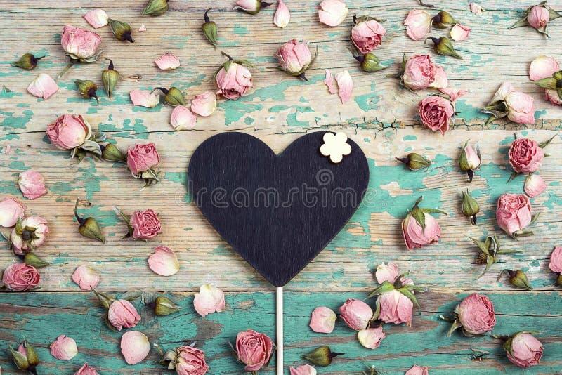 Coração-quadro-negro com as flores cor-de-rosa pequenas na turquesa wo velho fotos de stock royalty free