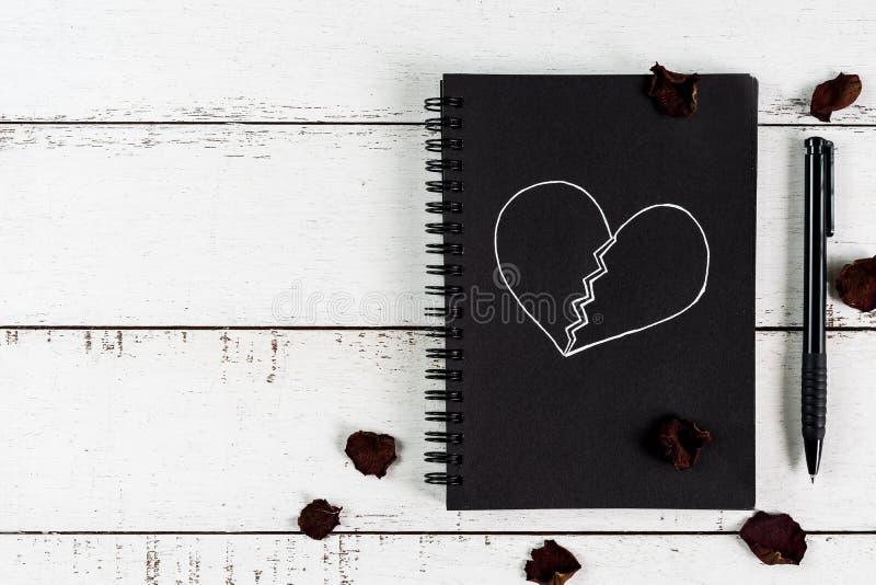Coração quebrado vermelho com a pétala cor-de-rosa e o caderno secados foto de stock