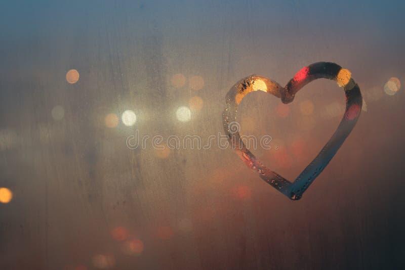Coração, tirado em um vidro misted, contra o contexto de uma rua da cidade da noite imagens de stock royalty free
