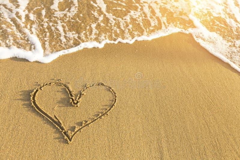 Coração tirado na areia da praia do mar, onda macia em um dia de verão ensolarado Amor fotos de stock royalty free
