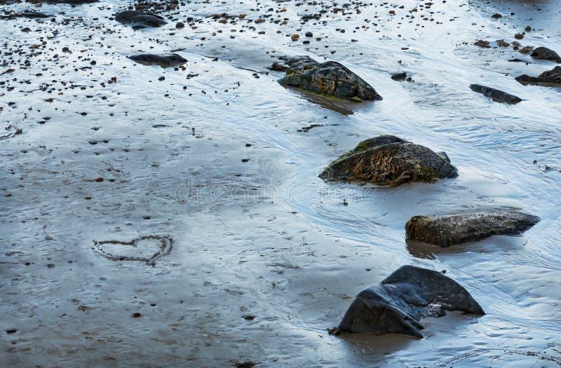 Coração tirado na areia de uma praia do mar foto de stock royalty free