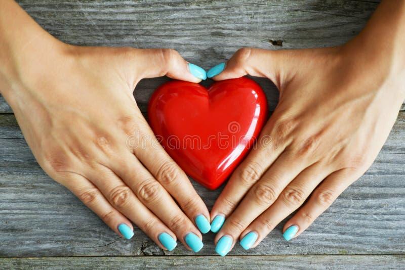 Coração vermelho como o símbolo do amor na mão da mulher no fundo de madeira rústico foto de stock