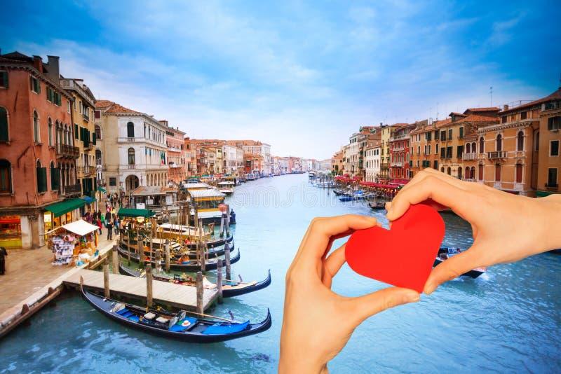 Coração vermelho da posse da mão sobre o canal grandioso em Veneza imagem de stock royalty free
