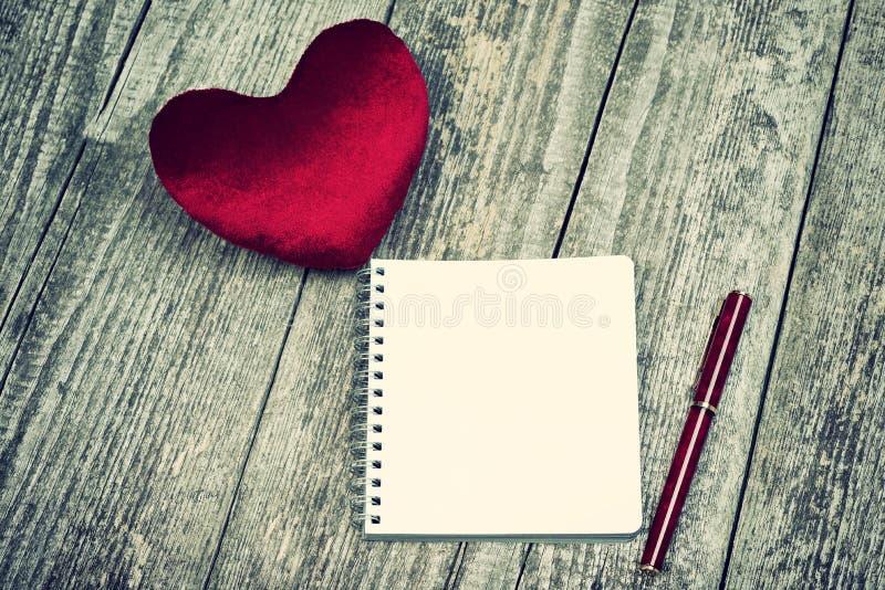 Coração vermelho da veludinha e bloco de notas vazio imagem de stock royalty free