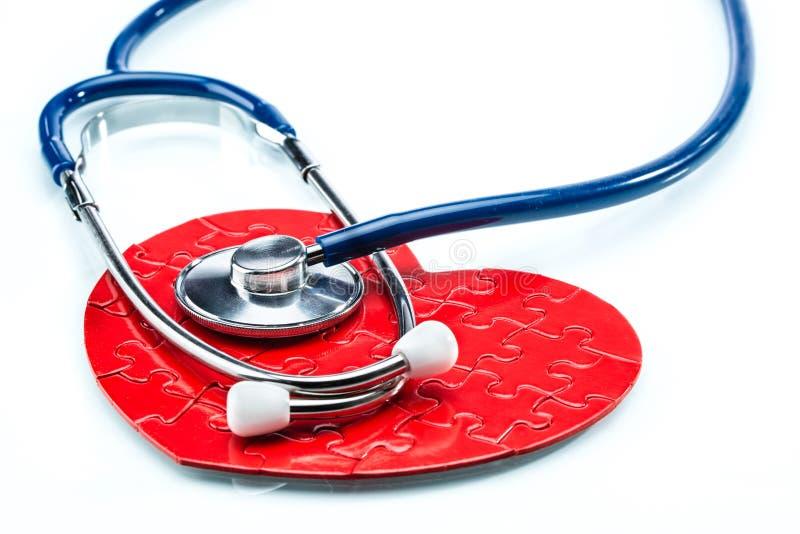 Coração vermelho do enigma com o estetoscópio isolado no fundo branco fotos de stock royalty free