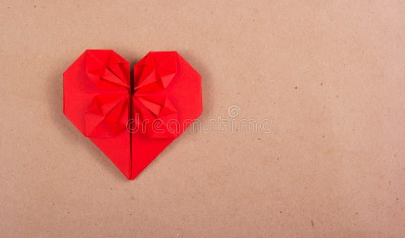 Coração vermelho do origâmi em um fundo de papel Valentim em um fundo do papel reciclado imagem de stock royalty free