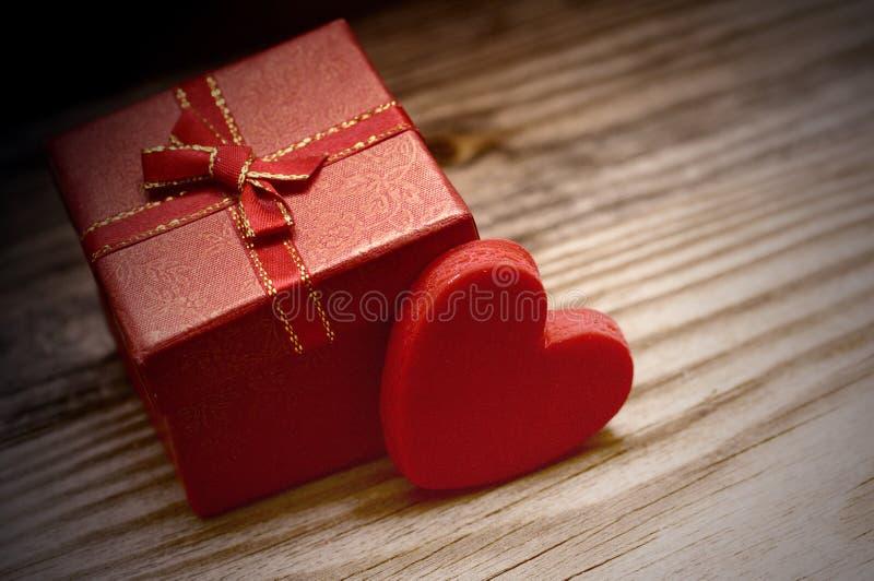 Coração vermelho e caixa de presente pequena com uma curva em um fundo de madeira imagens de stock