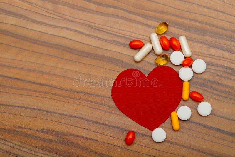 Coração vermelho e muitas drogas brilhantes dos comprimidos no fundo de madeira fotografia de stock royalty free