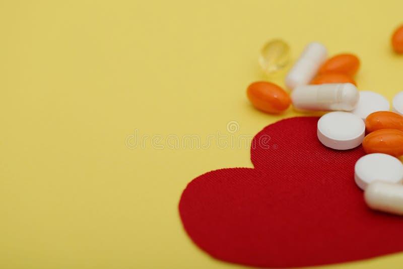Coração vermelho e muitos comprimidos brilhantes das drogas em um fundo amarelo fotos de stock