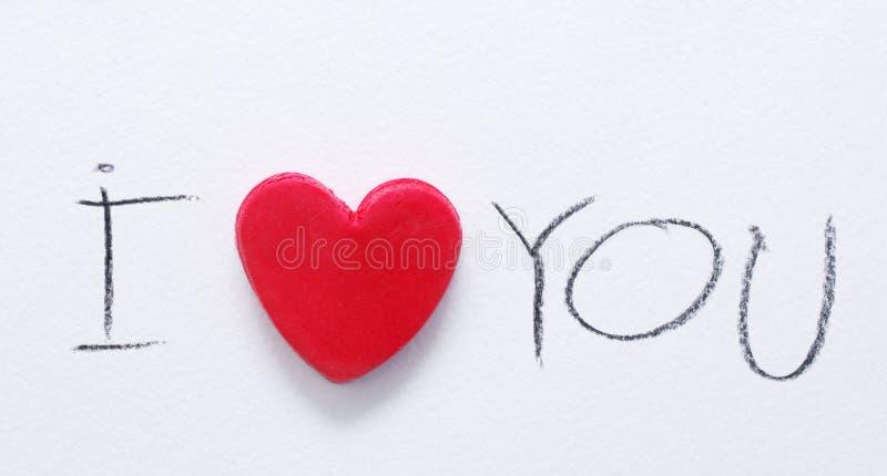 Coração vermelho e o texto eu te amo, escrito por um lápis vermelho no Livro Branco O dia de Valentim romântico do St do cartão foto de stock royalty free