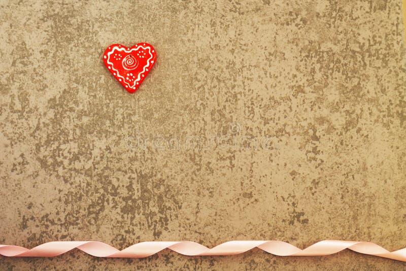 Coração vermelho em um fundo cinzento com fita imagem de stock royalty free