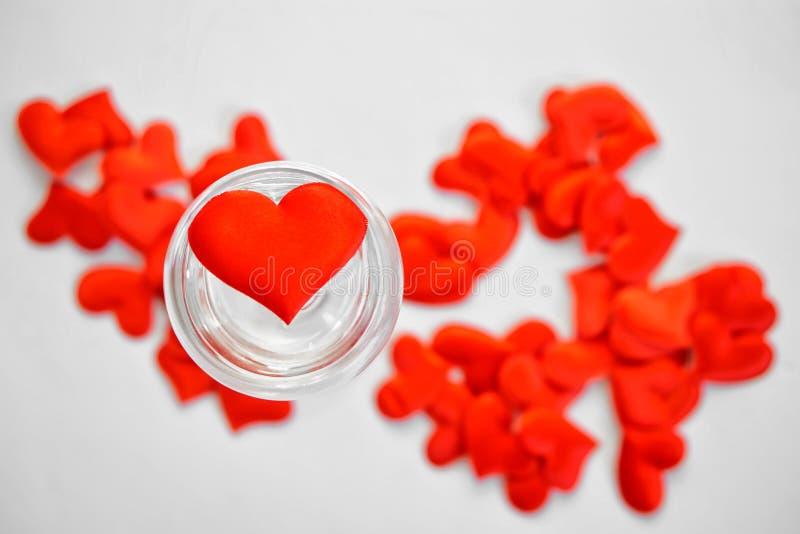 Coração vermelho em um vidro transparente enchido com água St Dia do ` s do Valentim fotografia de stock royalty free
