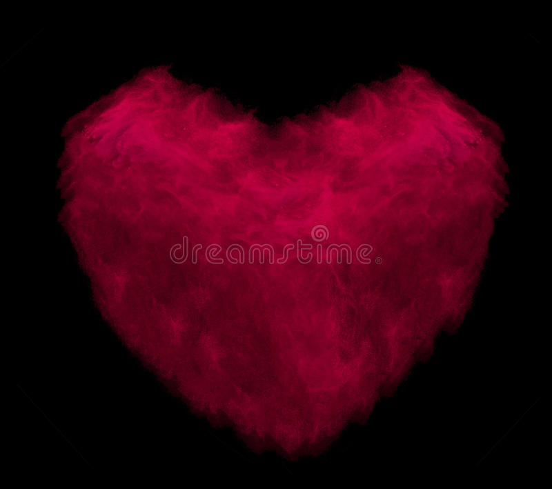 Coração vermelho feito da explosão do pó isolada no fundo preto imagens de stock