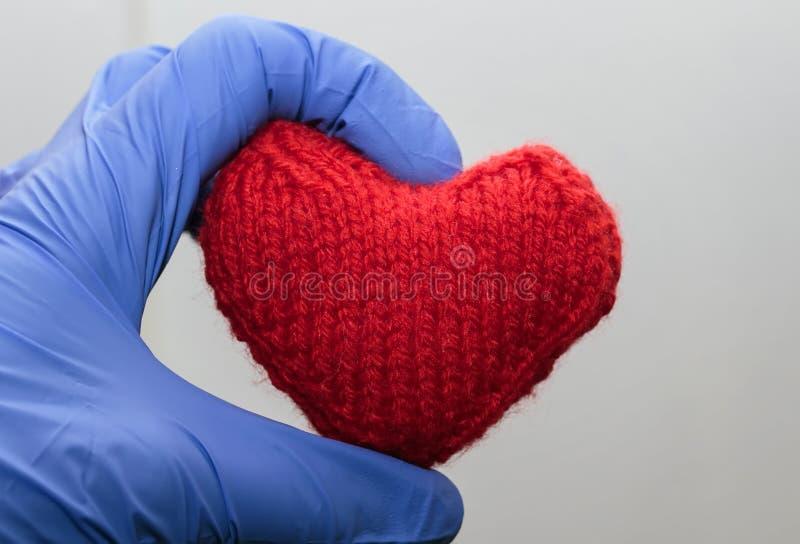 coração vermelho feito malha que guarda uma mão em luvas médicas fotografia de stock royalty free