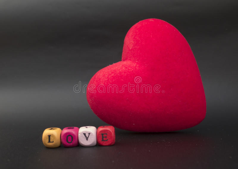 Coração vermelho no fundo preto com o subtítulo o AMOR do c imagens de stock royalty free