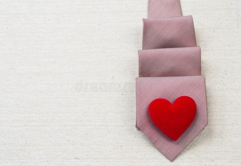 Coração vermelho no projeto vermelho da gravata do teste padrão no fundo da textura da lona fotos de stock royalty free