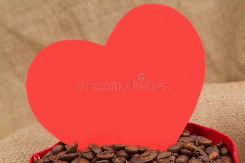 Coração vermelho no saco com feijões do coffe imagens de stock royalty free