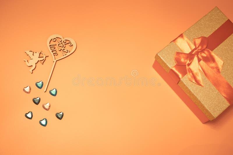 coração vermelho que dispara em um anjo, e muitos corações pequenos diferentes, e uma caixa vermelha com um presente com uma curv imagem de stock royalty free