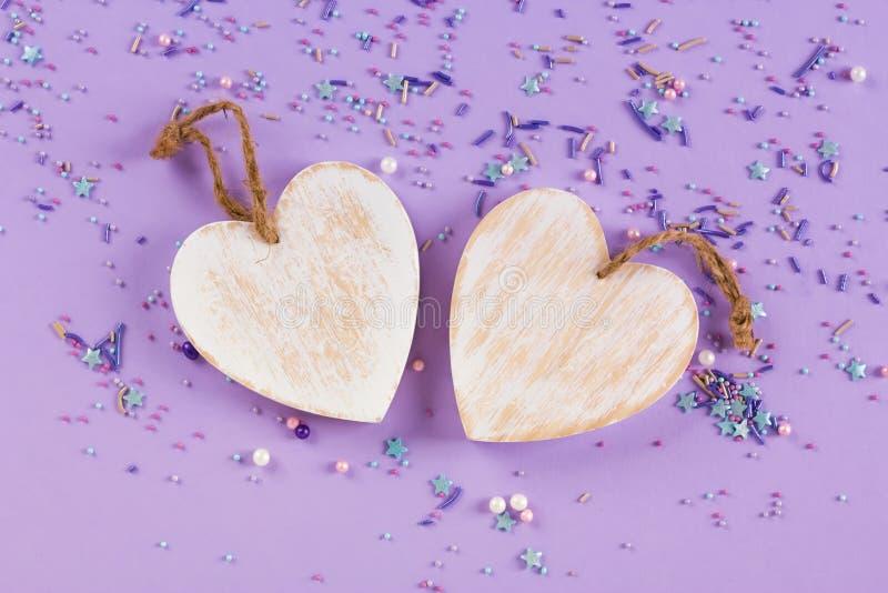 Corações brancos de madeira, estilo rústico, fundo roxo, decoração do dia de Valentim Fundo da vista superior imagem de stock