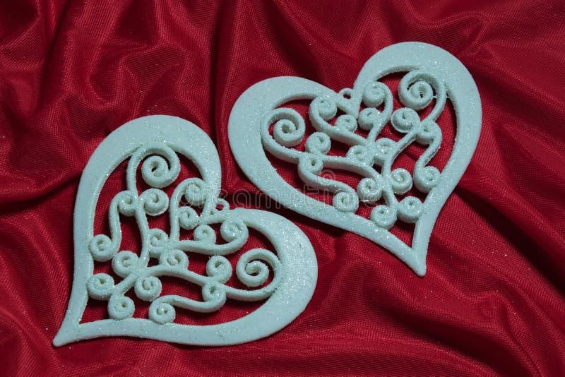 Corações brancos delicados bonitos em um fundo vermelho foto de stock royalty free