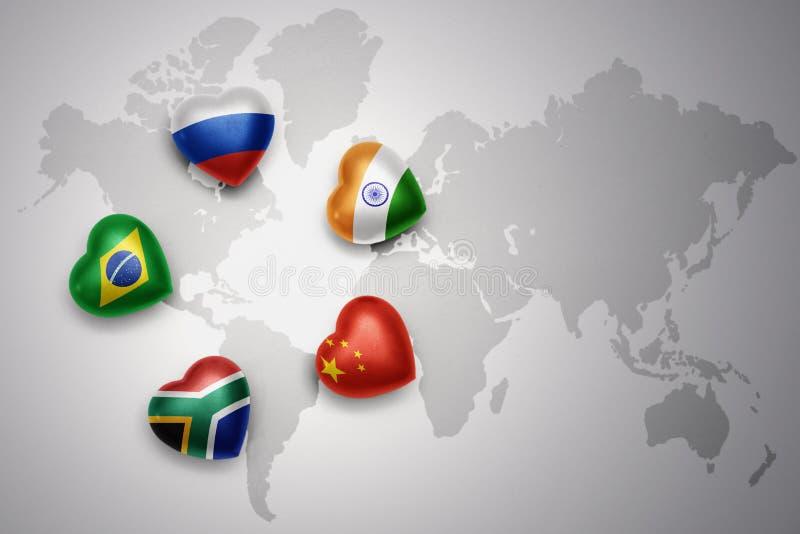 Corações com as bandeiras dos cinco países do brics, Rússia, Brasil, india, porcelana, África do Sul em um fundo do mapa do mundo ilustração do vetor