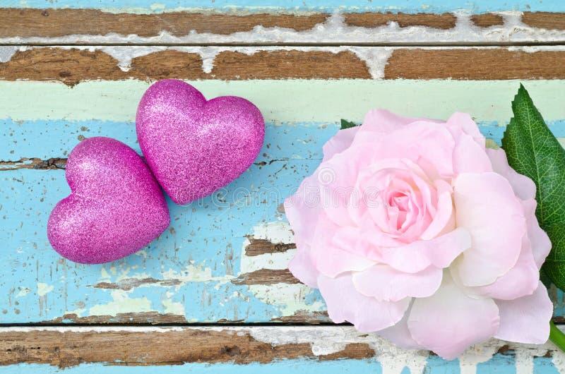 Corações cor-de-rosa e rosas cor-de-rosa na luz suja - backgroun de madeira azul fotos de stock royalty free