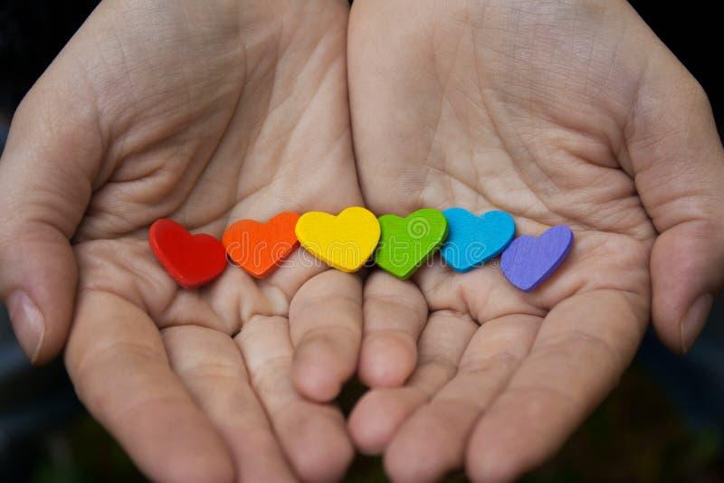 Corações da cor do arco-íris nas mãos do ` s das mulheres O LGBT S imagem de stock