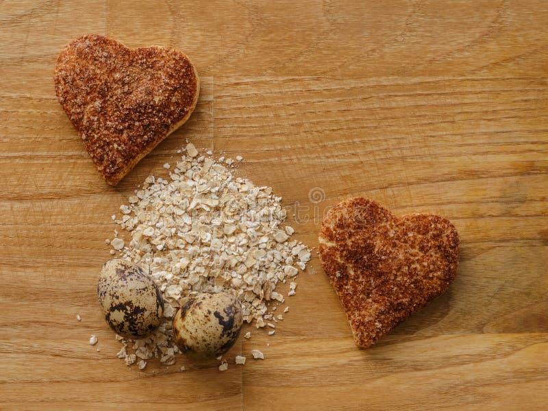 Corações da farinha de aveia e dos ovos e das cookies da canela na tabela de madeira fotos de stock