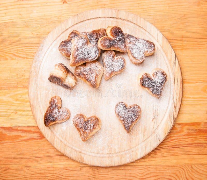 Corações da padaria da pastelaria da separação com pó do açúcar em de madeira fotografia de stock royalty free