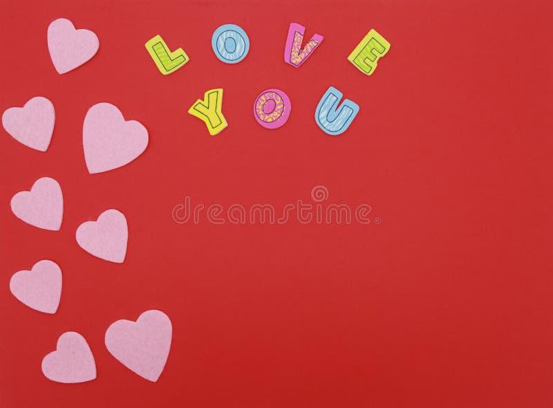 Corações de feltro no fundo vermelho com amor que você text imagens de stock
