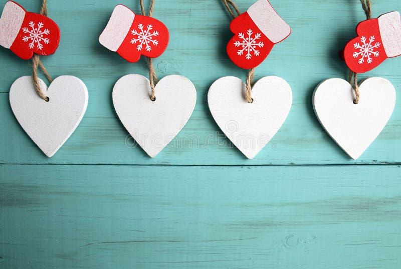 Corações de madeira brancos decorativos do Natal e mitenes vermelhos no fundo de madeira azul com espaço da cópia foto de stock