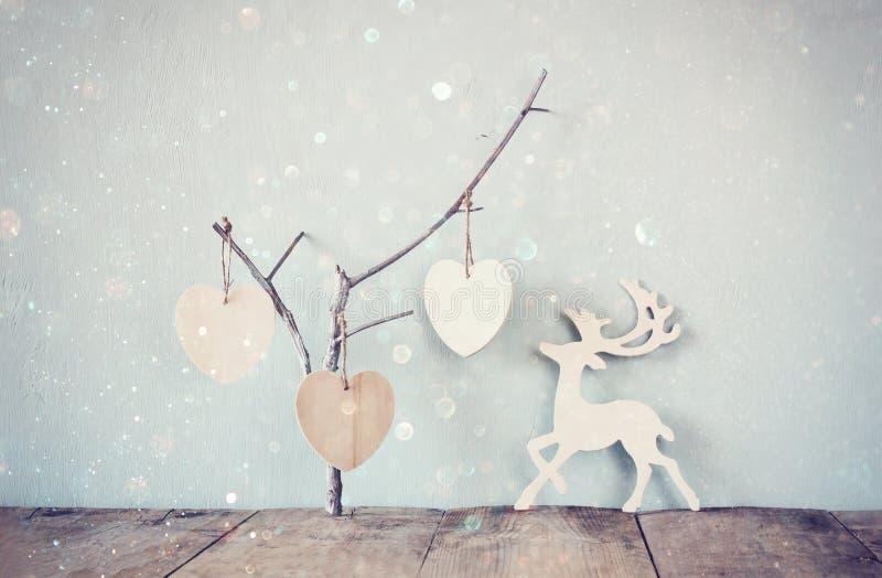 Corações de madeira de suspensão sobre e decoração de madeira dos cervos da chuva sobre o fundo de madeira imagem filtrada retro fotografia de stock royalty free