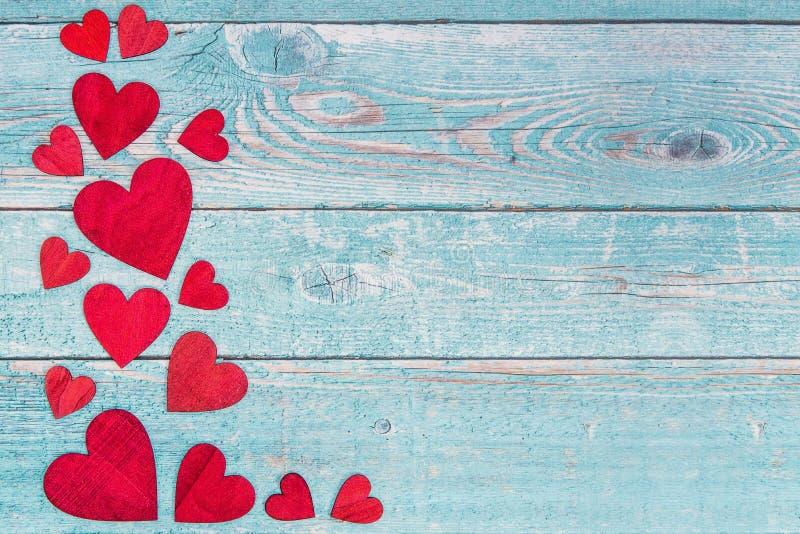 Corações de madeira vermelhos na beira esquerda em um fundo de madeira do andaime azul foto de stock