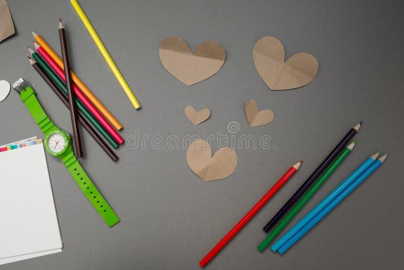 Corações de papel e lápis coloridos em um fundo cinzento imagens de stock