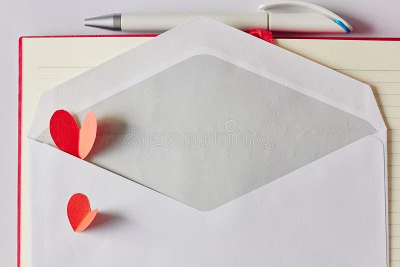 Corações de papel vermelhos no envelope, na pena e no caderno brancos fotografia de stock