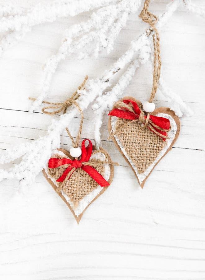 Corações decorativos no ramo coberto de neve imagens de stock