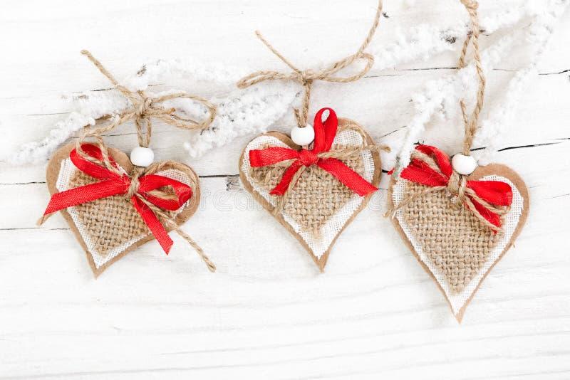 Corações decorativos no ramo coberto de neve no fundo de madeira imagens de stock royalty free