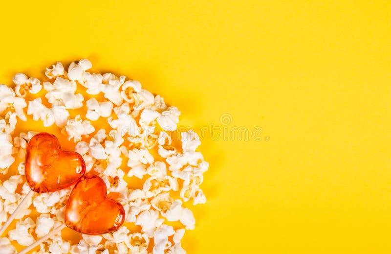 Corações deliciosos da pipoca e dos doces Pirulito e pipoca dispersada no fundo amarelo imagens de stock royalty free