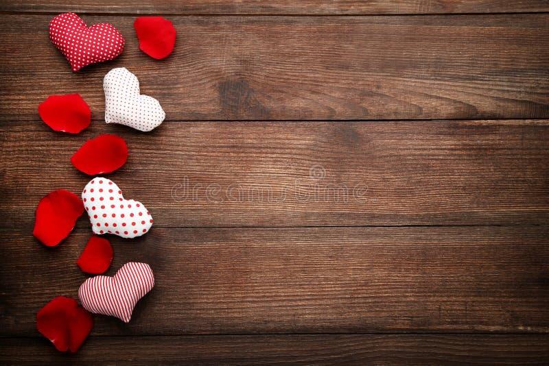 Corações do amor e pétalas cor-de-rosa vermelhas imagem de stock royalty free