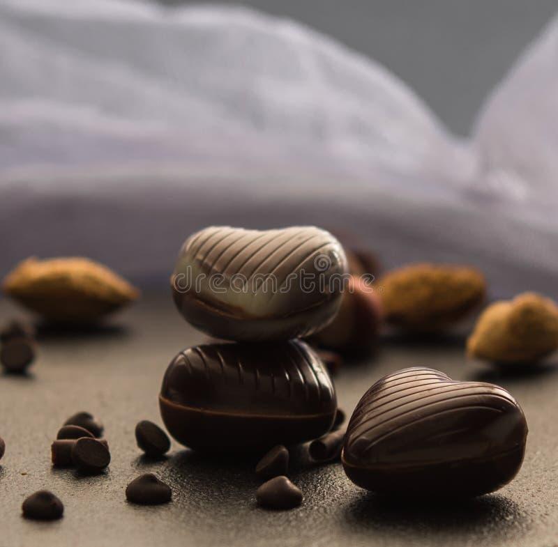 Corações do chocolate com fim escuro da luz do controle dos Valentim do amor da foto das porcas acima imagens de stock