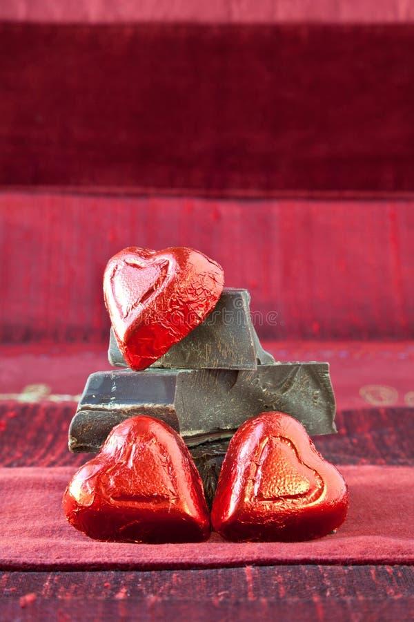 Corações dos doces em uma pilha de partes escuras do chocolate fotografia de stock royalty free