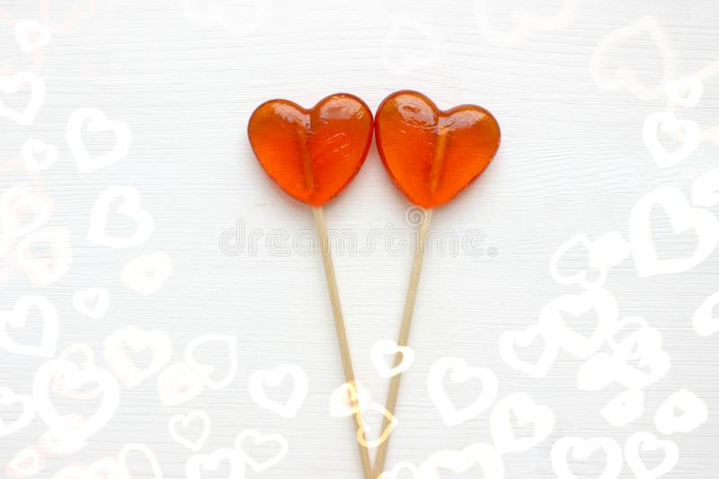 Corações dos doces O coração dois deu forma aos pirulitos isolados no fundo de madeira branco fotos de stock royalty free