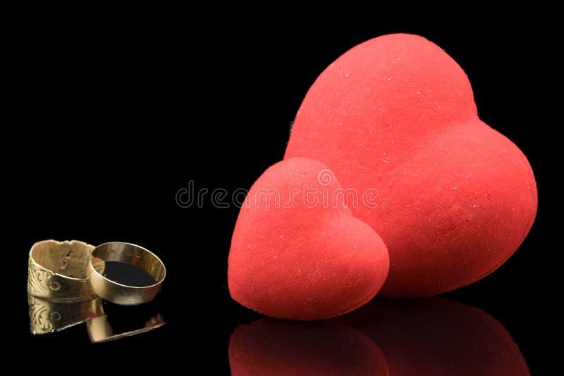 Corações e anéis de casamento imagens de stock