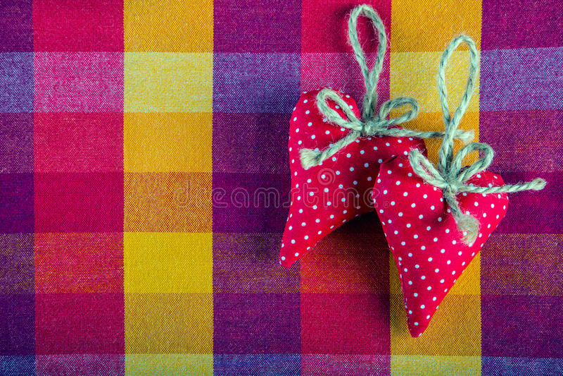Corações feitos a mão de pano dois vermelhos no guardanapo quadriculado de pano imagem de stock