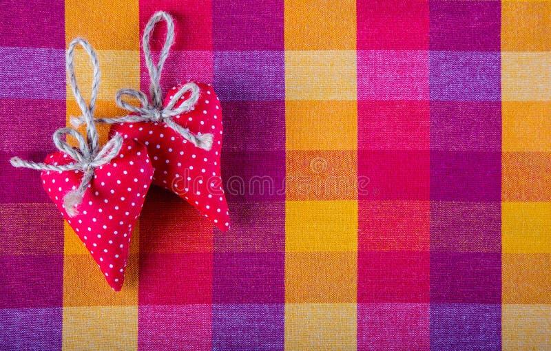 Corações feitos a mão de pano dois vermelhos no guardanapo quadriculado de pano foto de stock