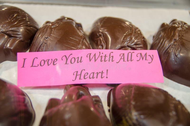 Corações humanos do chocolate escuro na janela da loja Figuras do chocolate fotografia de stock
