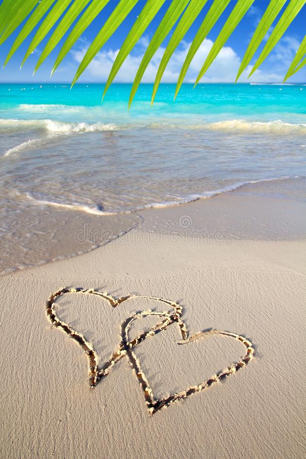 Corações no amor escrito na areia do Cararibe da praia fotografia de stock