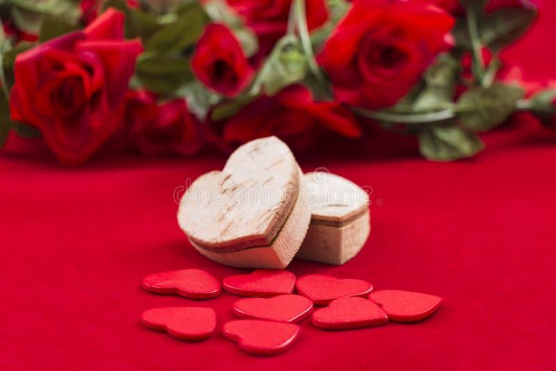 Corações no vermelho com as rosas no fundo fotos de stock royalty free