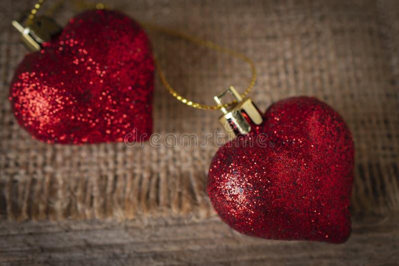 Corações plásticos vermelhos colocados no saco e na tabela de madeira imagens de stock