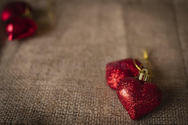 Corações plásticos vermelhos colocados no saco Há uns corações plásticos vermelhos colocados na parte traseira esquerda fotos de stock